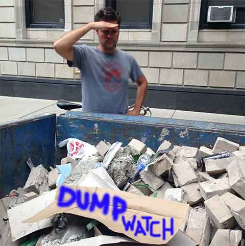 guy on a city street watching a blue dumpster