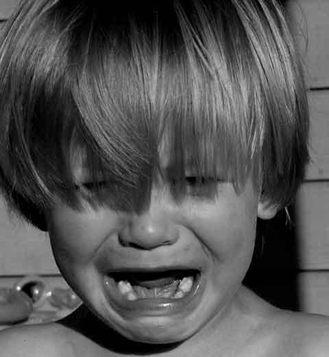 closeup shaggy haired kid crying