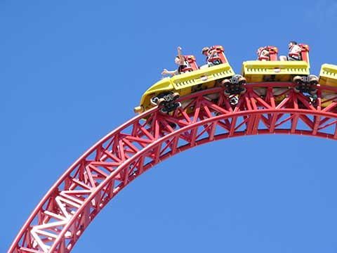 red roller coaster with yellow cars against blue sky
