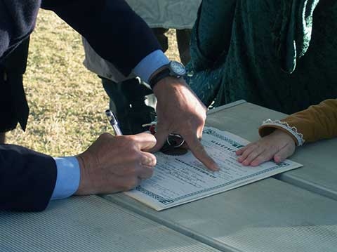 hands signing contract on picnic table
